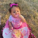 Face, Cheek, Lip, Dress, People In Nature, Baby & Toddler Clothing, Happy, Pink, Toddler, Grass, Baby, Child, Magenta, Fun, Recreation, Sitting, Fashion Accessory, Baby Products, Play, Sweetness, Person