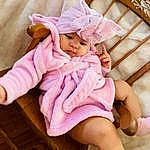 Skin, Leg, Purple, Dress, Baby & Toddler Clothing, Comfort, Sleeve, Pink, Baby, Finger, Toddler, Magenta, Linens, Thigh, Beauty, Bed, Sock, Peach, Sitting, Fashion Accessory, Person, Headwear