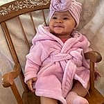 Clothing, Face, Cheek, Skin, Smile, Outerwear, Eyes, White, Leg, Purple, Baby & Toddler Clothing, Comfort, Sleeve, Baby, Pink, Headgear, Toddler, Chair, Wood, Person, Joy, Headwear
